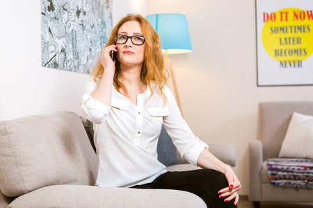 Business woman theme. Beautiful young woman with long curly red hair uses a mobile phone, calls and speaks sitting on the sofa in the house. Dressed in a white shirt and glasses for sight.