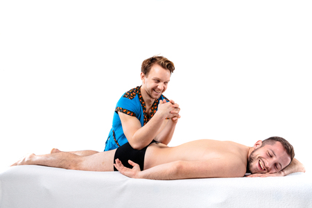 Theme massage and body care. Beautiful caucasian man in blue uniform and beard doing stretching, heals, diagnosis of back muscles guy with good figure on massage table in front of white background. Stock Photo