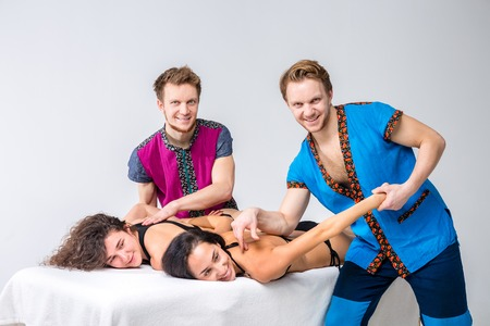 Theme massage and body care. Two young male twin brothers with a beard and uniform make a tandem massage in the hands of two sexy Caucasian women lying on a table on a white isolated background.