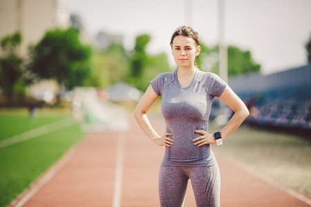 Portrait of a beautiful young caucasian woman with long hair in the tail and big breasts posing in gray sportswear standing training on a running stadium, a red rubber track in summer on a sunny day.