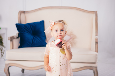 children's birthday. funny two-year-old Caucasian girl in pink dress standing to bedroom of house the background of couch and eating, holding cake dessert. Face and mouth smeared, smeared with cream.