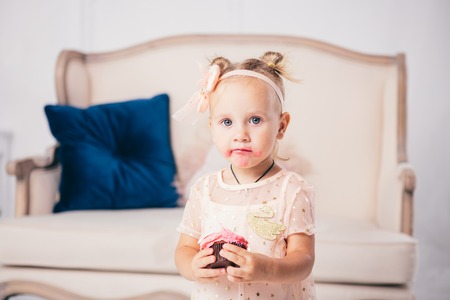 childrens birthday. funny two-year-old Caucasian girl in pink dress standing to bedroom of house the background of couch and eating, holding cake dessert. Face and mouth smeared, smeared with cream.