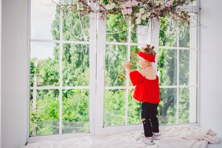 Little funny two years old baby girl in stylish red clothes and jeans and sneakers stands with back on the windowsill near the window. Headband and hairstyle on two heads in summer in sunny weather. Stock Photo