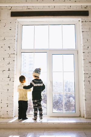 Theme Christmas morning. Two baby Caucasian boy and girl brother and sister standing with backs on window front of large box in embrace in winter knitted woolen clothes and hat of house in sunny day. Stockfoto