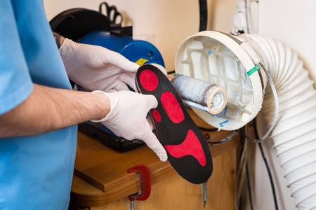 The process of manufacturing orthopedic individual insoles for people with leg diseases, flat feet. Close-up of a man's hand of an employee urges an orthopedic insole on a machine tool in a workshop. Stok Fotoğraf