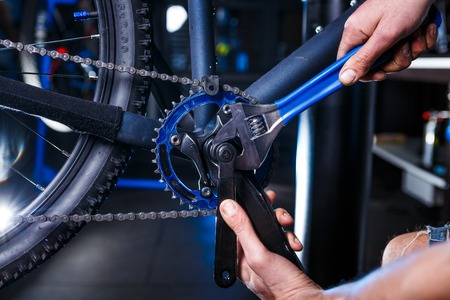 A close-up of a male bicycle mechanic's hand in the workshop uses a screwdriver tool to adjust and repair the bicycle crank assembly, the front bike stars in the bicycle store