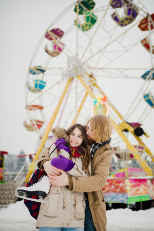 Young couple in love with a happy young man with a beard and a woman on a background of a fucking colossus, a Ferris wheel resting, a date in an amusement park in the winter in the Christmas holidays. Фото со стока