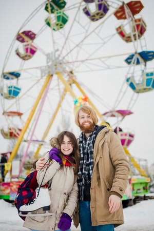 Young couple in love with a happy young man with a beard and a woman on a background of a colossus, a Ferris wheel resting, a date in an amusement park in the winter in the Christmas holidays.