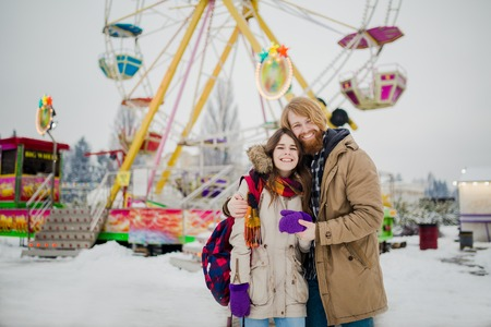 Young couple in love with a happy young man with a beard and a woman on a background of a fucking colossus, a Ferris wheel resting, a date in an amusement park in the winter in the Christmas holidays. Stockfoto
