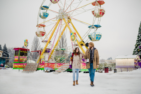 Young couple in love with a happy young man with a beard and a woman on a background of a fucking colossus, a Ferris wheel resting, a date in an amusement park in the winter in the Christmas holidays. 版權商用圖片