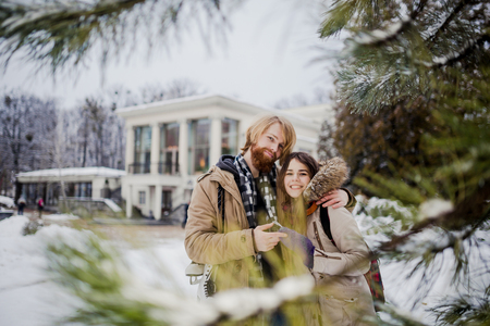 Young loving couple Caucasian man with blond long hair and beard, woman with toothy smile have fun, indulge, fool around winter park near Christmas tree, coniferous tree after ice skating in winter.