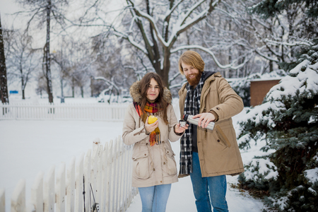Young loving couple caucasian man with blond long hair and beard, beautiful woman have fun drinking a hot drink from bottle, eating green apple in snow park near white fence and coniferous tree. Stock Photo