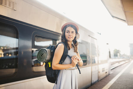 theme railway and travel. Portrait young caucasian woman with toothy smile standing at train station train background with backpack and equipment for tourism isolated mat in dress and hat in summer.