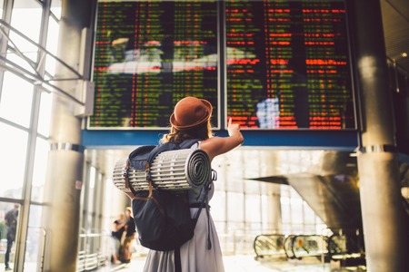 Theme travel public transport. young woman standing back in dress and hat behind backpack camping equipment for sleeping, insulating mat looks schedule on scoreboard airport station hand to the front.
