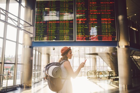 Theme travel and tranosport. Beautiful young caucasian woman in dress and backpack standing inside train station or terminal looking at a schedule holding a red phone, uses communication technology. Imagens