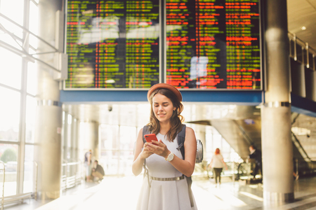 Theme travel and tranosport. Beautiful young caucasian woman in dress and backpack standing inside train station or terminal looking at a schedule holding a red phone, uses communication technology. Archivio Fotografico