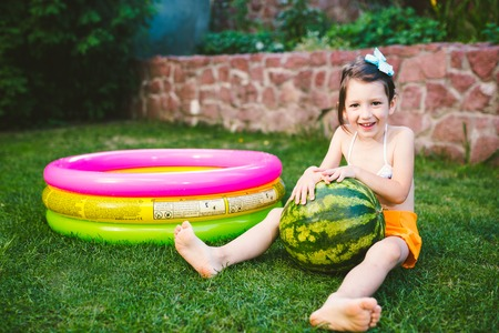 The topic proper healthy eating children. Little baby girl 4 years old caucasian sitting on green grass hugging big green round berries watermelon near children's inflatable pool in yard of house.
