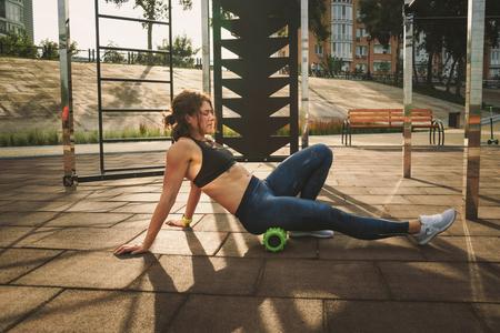 Themensport und Rehabilitationssportmedizin. Schöne starke schlanke kaukasische Sportlerin verwendet Schaumstoffrolle Green Field Street Workout, um Schmerzen zu beseitigen, Muskeln zu dehnen und zu massieren.