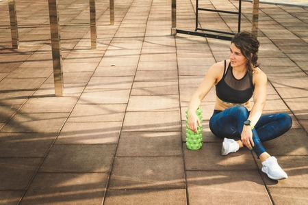 theme sport and rehabilitation sports medicine. Beautiful strong slender Caucasian woman athlete sits next foam roller green field street workout to remove the pain, stretch and massage muscles.