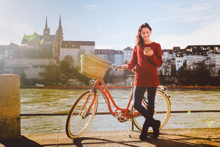 theme tourism on bicycle and modern technology. Beautiful young caucasian woman stands near red retro bicycle on riverside river Rhine Basel Swiss winter warm sunny weather uses the phone in hand.