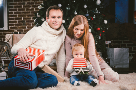 Family celebratory Christmas evening. Family three Caucasian people sitting under coniferous tree Christmas tree on floor of carpet wool. A child holds box with gift, parents young stylishly dressed. Standard-Bild - 115334933