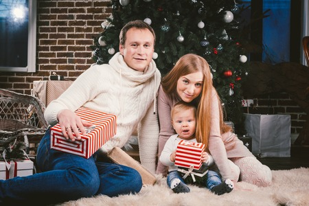 Family celebratory Christmas evening. Family three Caucasian people sitting under coniferous tree Christmas tree on floor of carpet wool. A child holds box with gift, parents young stylishly dressed. Standard-Bild - 115334935