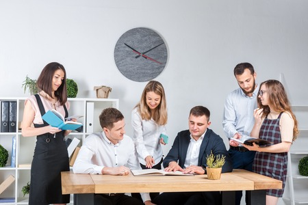 Theme is business and teamwork. A group of young Caucasian people office workers holding a meeting, briefing, working with papers and documents in a light office office around a wooden table. Standard-Bild - 119304214
