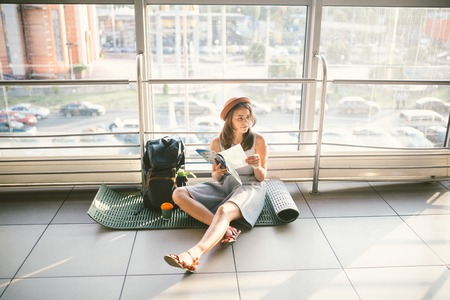 Waiting, delayed transport in the terminal of the airport or train station. Young caucasian woman in dress and hat sits on tourist rug with backpack near window to room and looks into tourist map.. Standard-Bild - 115331215