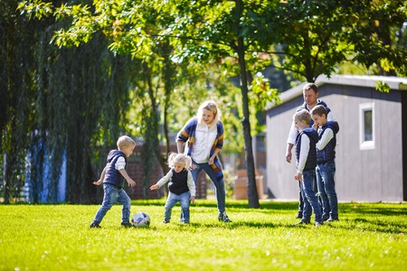 The theme family outdoor activities. big friendly Caucasian family of six mom dad and four children playing football, running with the ball on lawn, green grass lawn near the house on a sunny day. Standard-Bild - 115331566