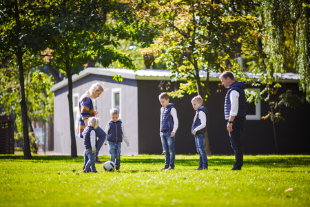 The theme family outdoor activities. big friendly Caucasian family of six mom dad and four children playing football, running with the ball on lawn, green grass lawn near the house on a sunny day. Standard-Bild - 115331614