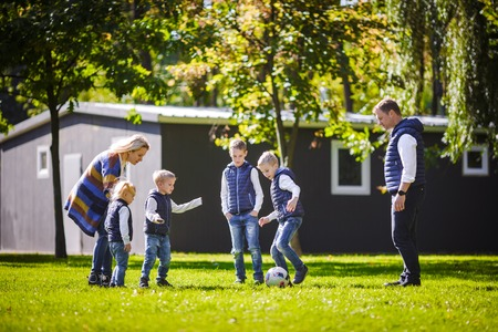 The theme family outdoor activities. big friendly Caucasian family of six mom dad and four children playing football, running with the ball on lawn, green grass lawn near the house on a sunny day. Standard-Bild - 115331629