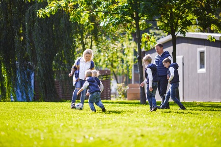 The theme family outdoor activities. big friendly Caucasian family of six mom dad and four children playing football, running with the ball on lawn, green grass lawn near the house on a sunny day. Standard-Bild - 115331656