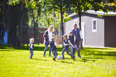 The theme family outdoor activities. big friendly Caucasian family of six mom dad and four children playing football, running with the ball on lawn, green grass lawn near the house on a sunny day. Standard-Bild - 115331699
