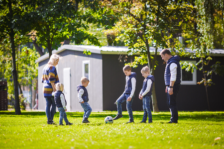 The theme family outdoor activities. big friendly Caucasian family of six mom dad and four children playing football, running with the ball on lawn, green grass lawn near the house on a sunny day. Standard-Bild - 115331721