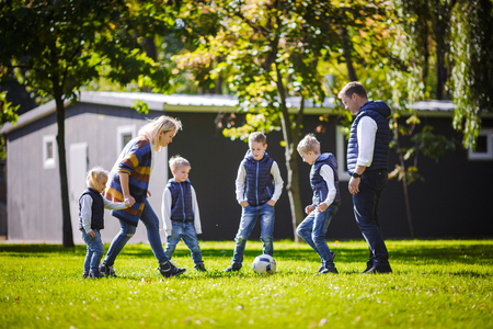 The theme family outdoor activities. big friendly Caucasian family of six mom dad and four children playing football, running with the ball on lawn, green grass lawn near the house on a sunny day. Standard-Bild - 115332240