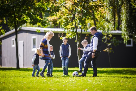 The theme family outdoor activities. big friendly Caucasian family of six mom dad and four children playing football, running with the ball on lawn, green grass lawn near the house on a sunny day. Standard-Bild - 115332426