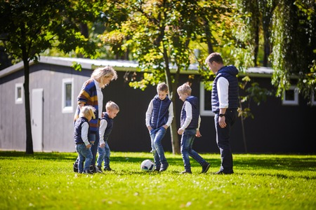 The theme family outdoor activities. big friendly Caucasian family of six mom dad and four children playing football, running with the ball on lawn, green grass lawn near the house on a sunny day. Standard-Bild - 115332526