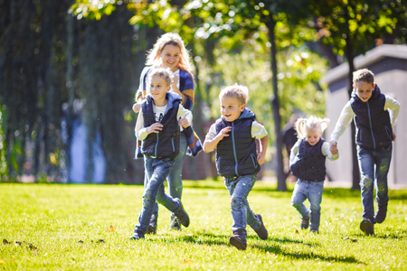The theme family outdoor activities. big friendly Caucasian family of six mom dad and four children playing football, running with the ball on lawn, green grass lawn near the house on a sunny day. Standard-Bild - 115333172