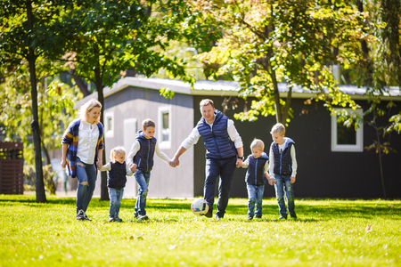 The theme family outdoor activities. big friendly Caucasian family of six mom dad and four children playing football, running with the ball on lawn, green grass lawn near the house on a sunny day. Standard-Bild - 115333223