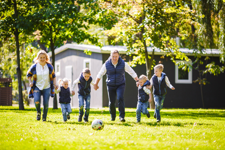 The theme family outdoor activities. big friendly Caucasian family of six mom dad and four children playing football, running with the ball on lawn, green grass lawn near the house on a sunny day. Standard-Bild - 115333265