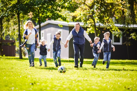 The theme family outdoor activities. big friendly Caucasian family of six mom dad and four children playing football, running with the ball on lawn, green grass lawn near the house on a sunny day. Standard-Bild - 115333322