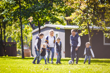 The theme family outdoor activities. big friendly Caucasian family of six mom dad and four children playing football, running with the ball on lawn, green grass lawn near the house on a sunny day. Standard-Bild - 115333348