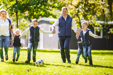 The theme family outdoor activities. big friendly Caucasian family of six mom dad and four children playing football, running with the ball on lawn, green grass lawn near the house on a sunny day. Standard-Bild - 115333390