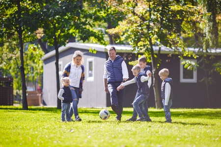 The theme family outdoor activities. big friendly Caucasian family of six mom dad and four children playing football, running with the ball on lawn, green grass lawn near the house on a sunny day. Standard-Bild - 115333421