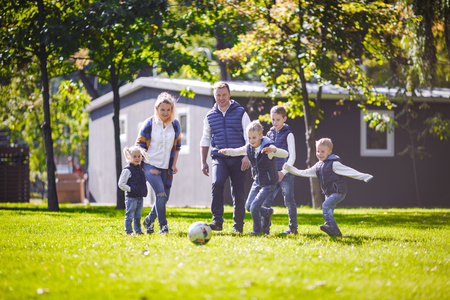The theme family outdoor activities. big friendly Caucasian family of six mom dad and four children playing football, running with the ball on lawn, green grass lawn near the house on a sunny day. Standard-Bild - 115333458