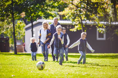 The theme family outdoor activities. big friendly Caucasian family of six mom dad and four children playing football, running with the ball on lawn, green grass lawn near the house on a sunny day. Standard-Bild - 115333489
