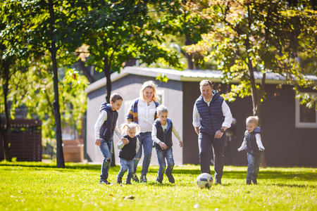 The theme family outdoor activities. big friendly Caucasian family of six mom dad and four children playing football, running with the ball on lawn, green grass lawn near the house on a sunny day. Standard-Bild - 115333553