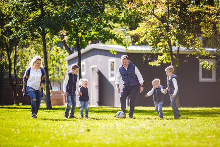 The theme family outdoor activities. big friendly Caucasian family of six mom dad and four children playing football, running with the ball on lawn, green grass lawn near the house on a sunny day. Standard-Bild - 115333584