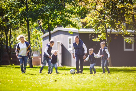 The theme family outdoor activities. big friendly Caucasian family of six mom dad and four children playing football, running with the ball on lawn, green grass lawn near the house on a sunny day. Standard-Bild - 115333604