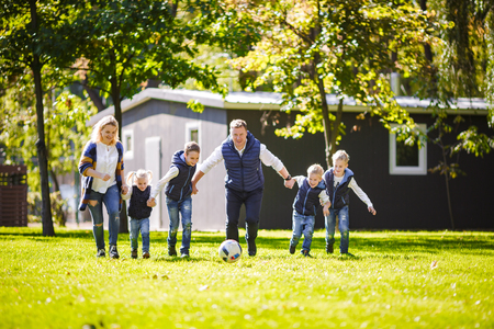 The theme family outdoor activities. big friendly Caucasian family of six mom dad and four children playing football, running with the ball on lawn, green grass lawn near the house on a sunny day. Standard-Bild - 115333657
